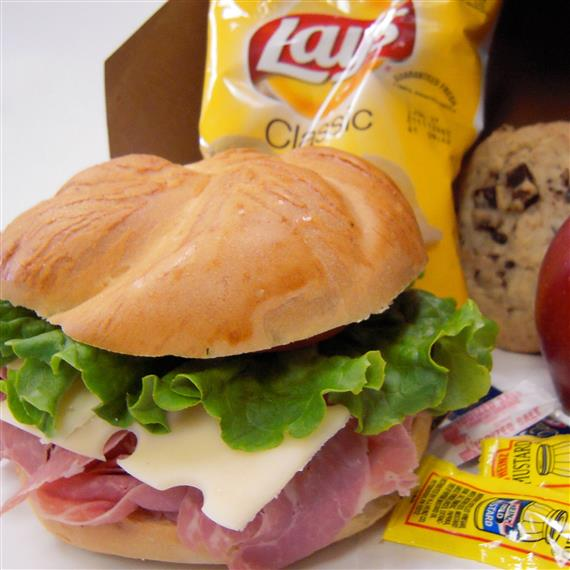 ham and swiss sandwich served on a bun with a side of potato chips and a cookie