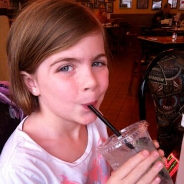little girl drinking a cup of water through a straw