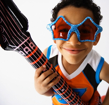 little boy wearing star sunglasses and playing a blow up guitar