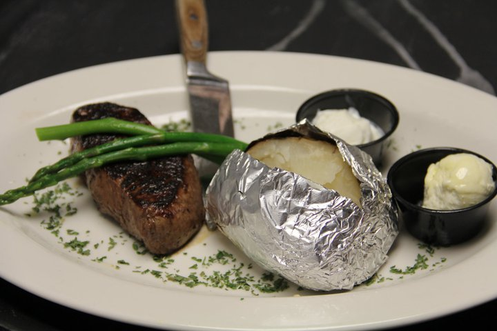 grilled strip steak topped with asparagus. baked potato on the side with butter and sour cream.