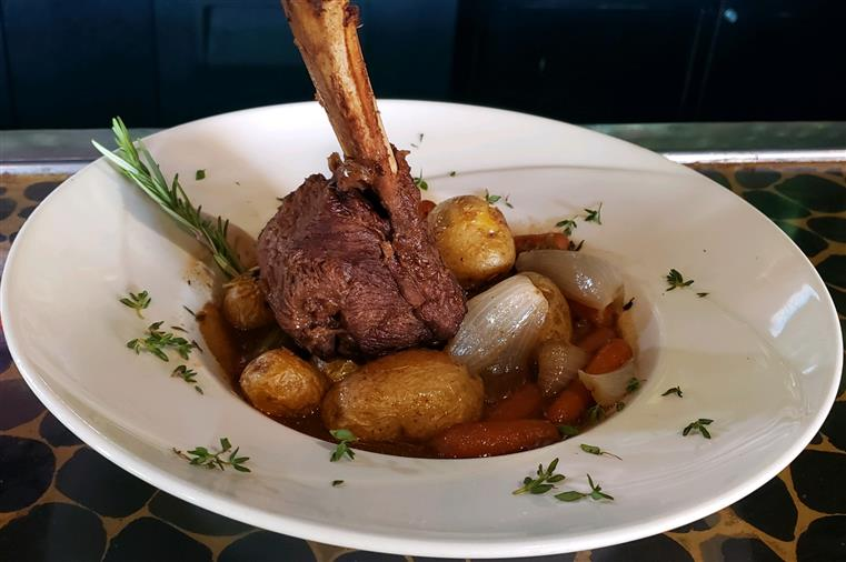 beef on the bone in a stew of potatoes, carrots and onions.