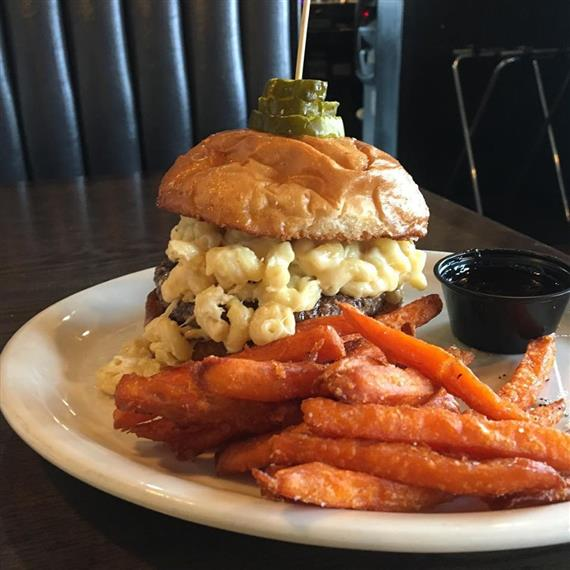 Cheeseburger topped with macaroni and cheese and pickles with a side of sweet potato fries