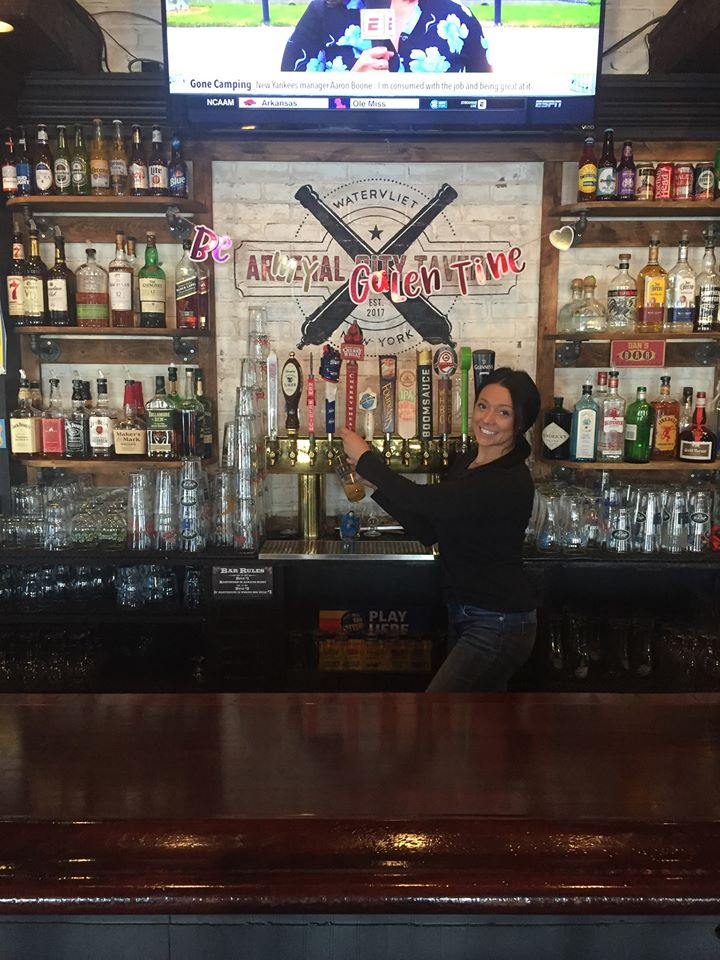 A bartender standing in front of the tap beer options