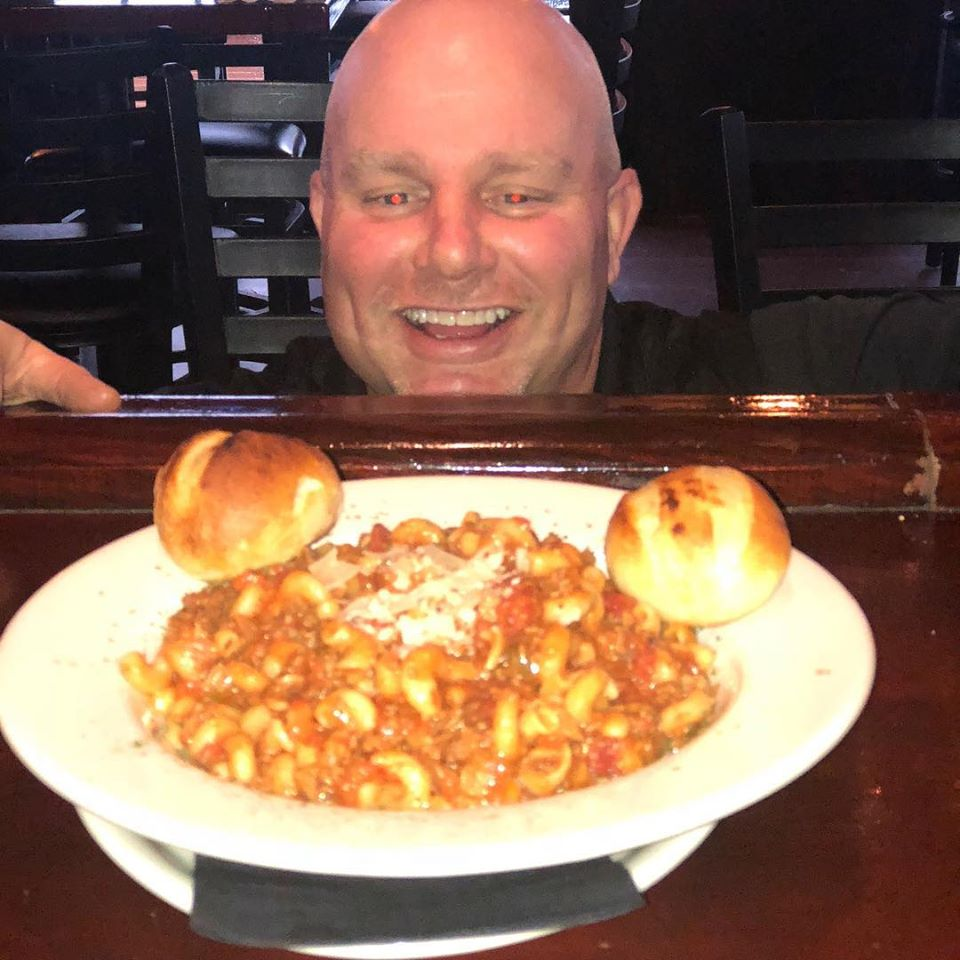 Dan smiling behind a plate of pasta Bolognese
