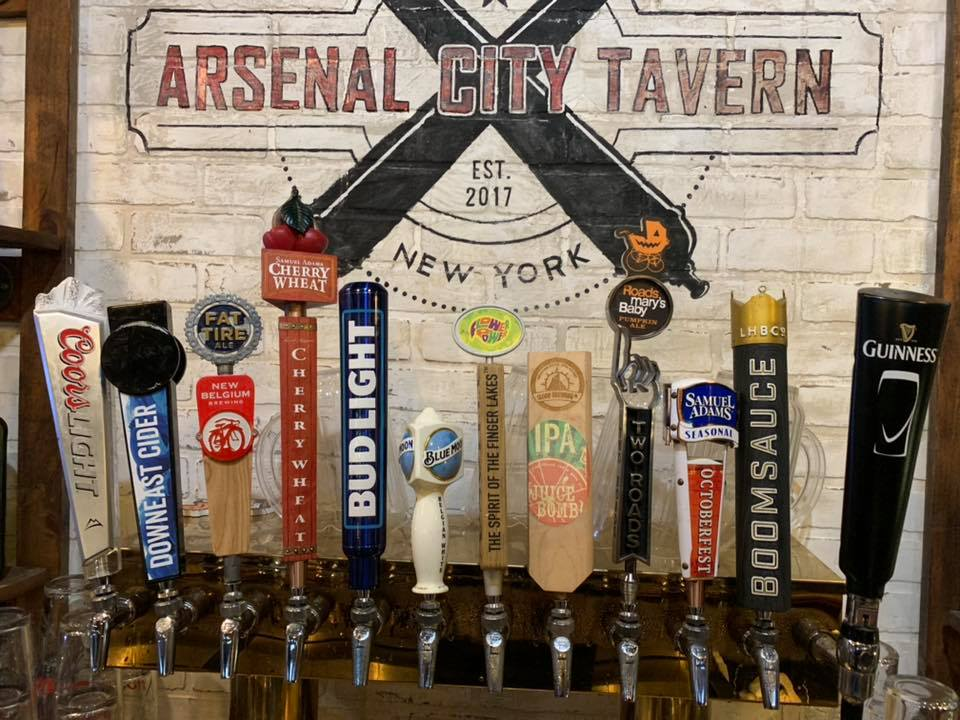 Beer taps in front of a Brick wall with Arsenal city Tavern painted on it.