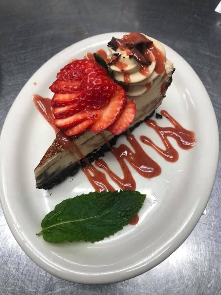 A sliver of cake topped with strawberry syrup, fresh strawberries, and a mint leaf garnish