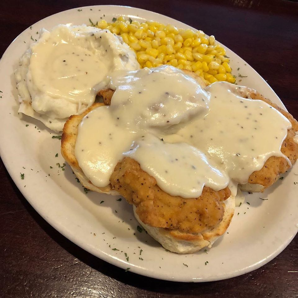 Biscuits covered in gravy with a side of mashed potatoes and corn