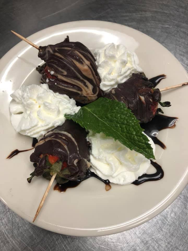 Chocolate dipped strawberries topped with whipped cream and a mint leaf garnish