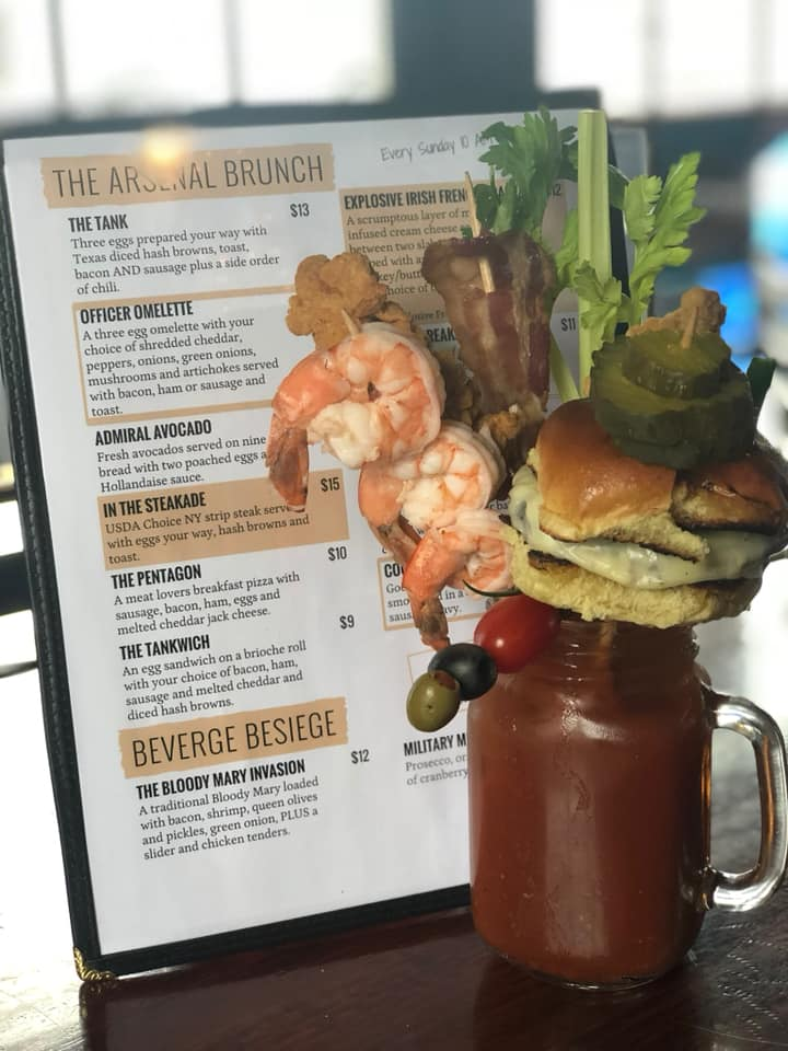 A bloody Mary topped with shrimp, bacon, celery, and a mini cheeseburger sider on a stick