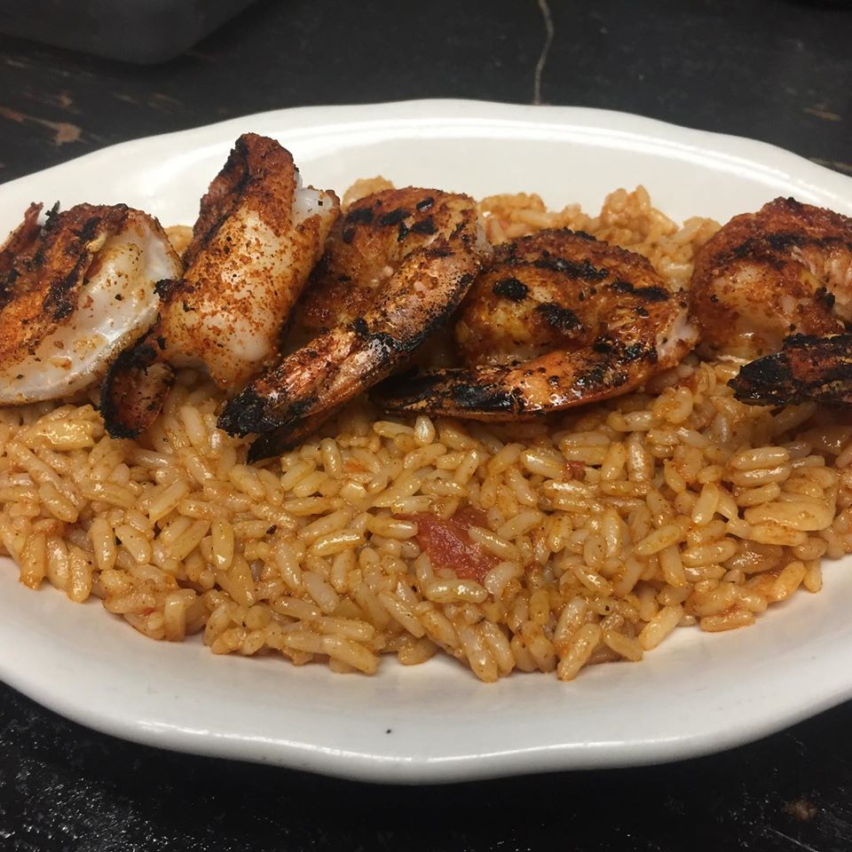 Rice topped with blackened and seasoned shrimp
