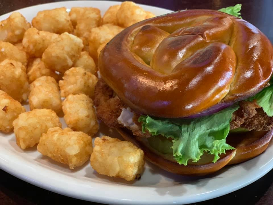 Fried chicken sandwich with a pretzel bun and a side of tater tots