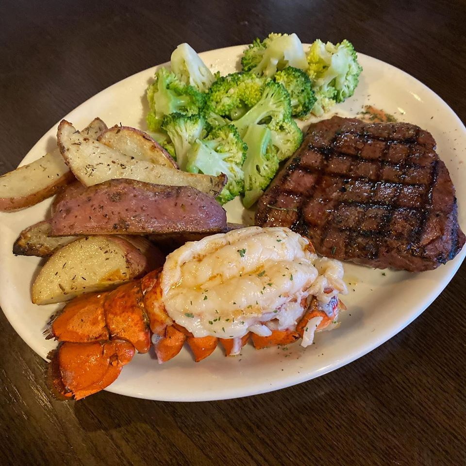 Steak and lobster dinner with a side of wedged potatoes and cooked broccoli