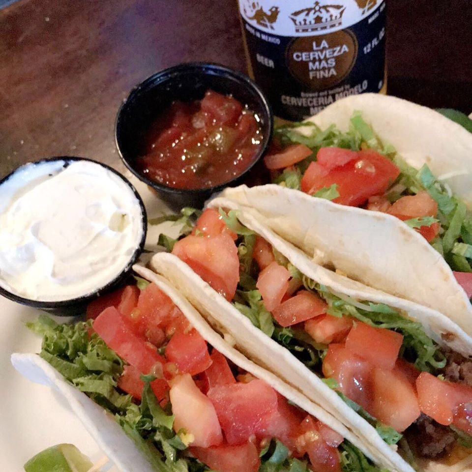 Tacos topped with tomatoes and lettuce, with a side of salsa and sour cream
