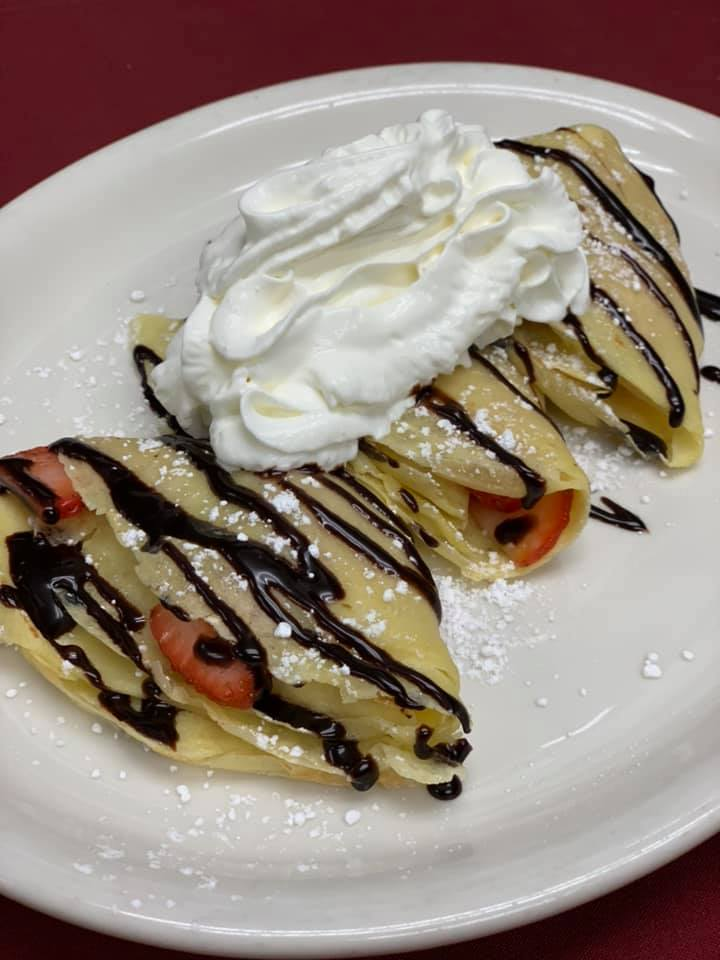 Crepes with chocolate drizzle, powdered sugar, strawberries, and whipped cream on top