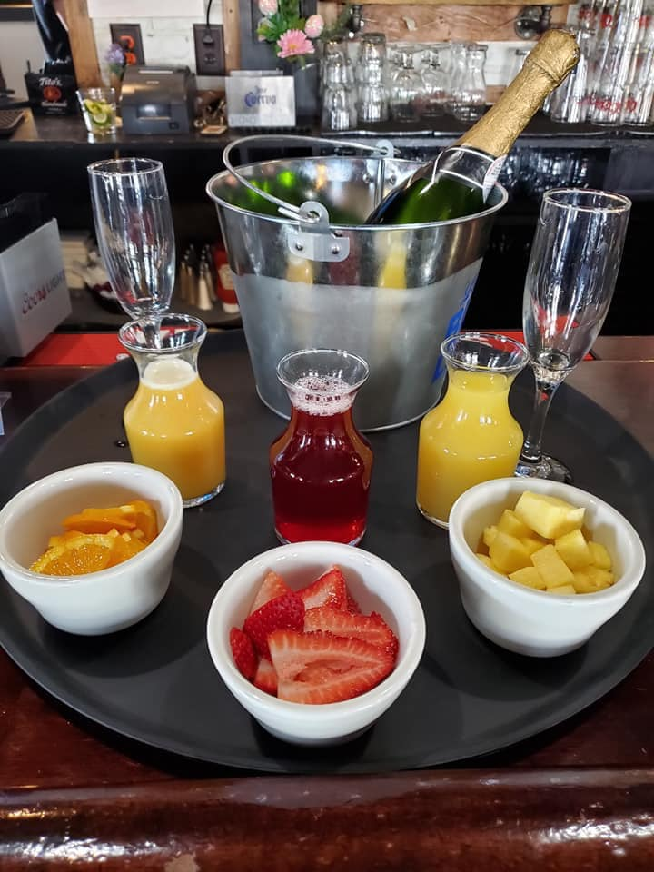 A mimosa display with juices and fruit at a catered event