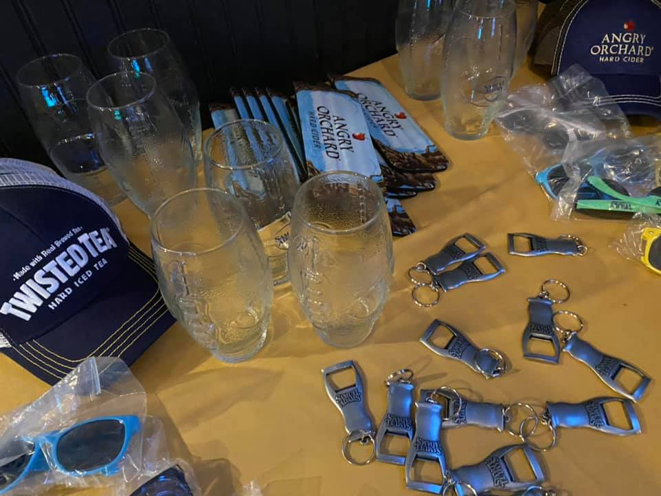 Angry Orchard and Twisted Tea merchandise on a table at a catered event