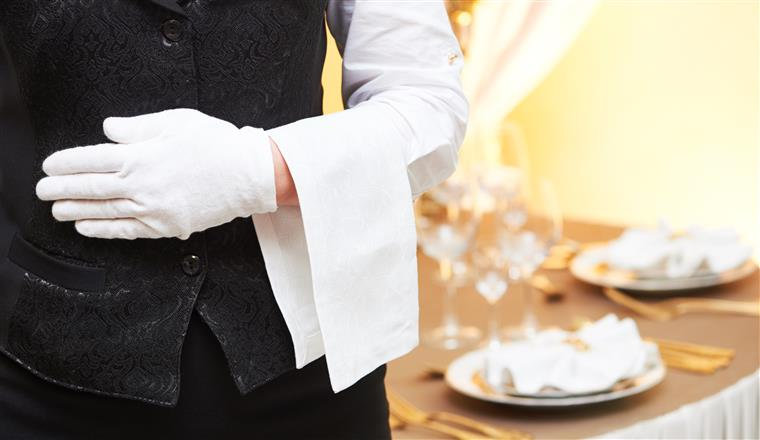 wait staff wearing a linen uniform and holding a linen napkin
