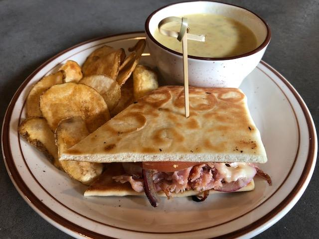 Panini Sandwich on flatbread served with chips and a side sauce