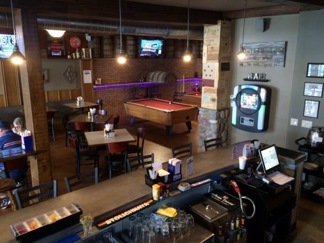 Bar hall with pool tables at the back, tables all around and a bar counter on one side