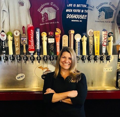 Owner Tammy standing in front of the tap handles behind the bar