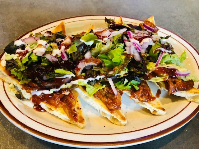 BBQ Pork Flatbread: Slow smoked pulled pork smothered in Doghouse BBQ sauce with red onions and spring mix. Served on our fresh flatbread