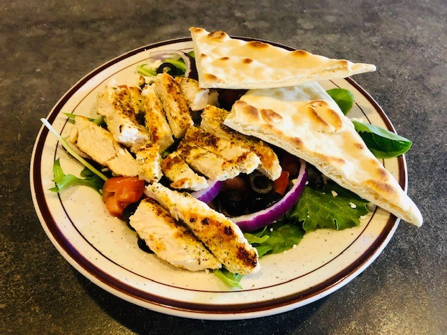 Greek Salad: Acadia blend lettuce topped with feta cheese, tomatoes, red onions, black olives and Greek dressing. Served with warm flat bread and grilled chicken