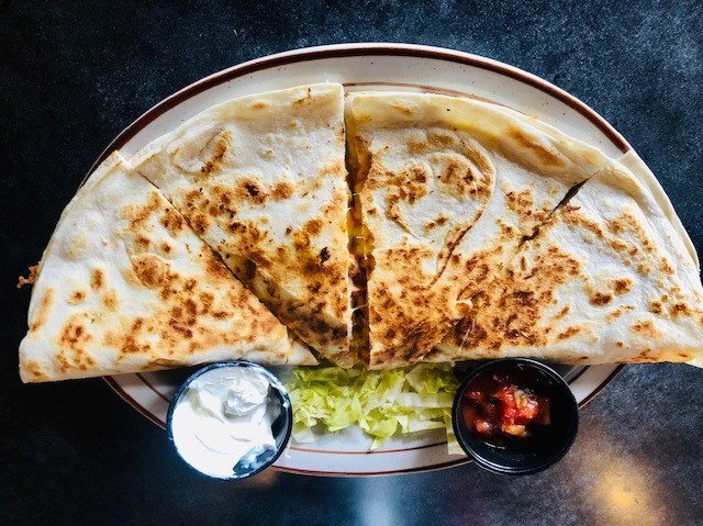 Chicken Quesadilla: A jumbo white tortilla stuffed with diced grilled chicken, onions, tomatoes, green peppers and cheddar jack cheese. Served with salsa and sour cream
