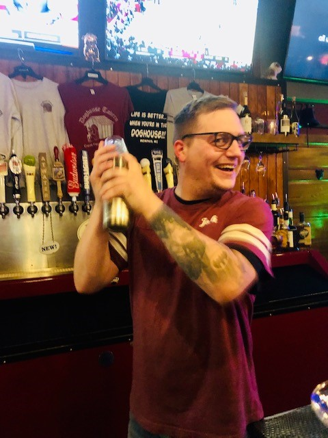 Bartender smiling and shaking a cocktail