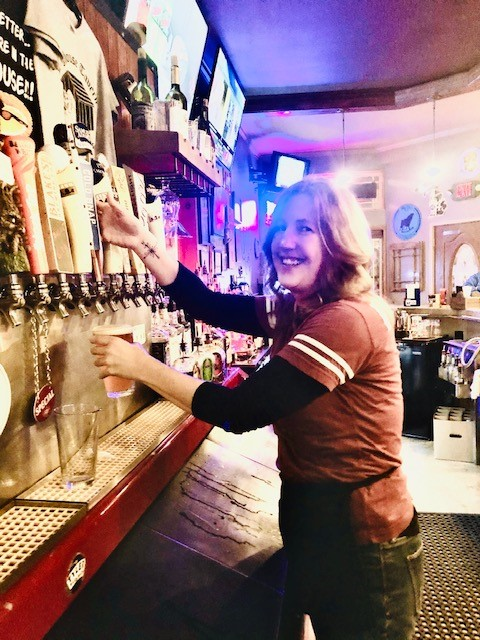 a lady filling up a glass with a beer on tap