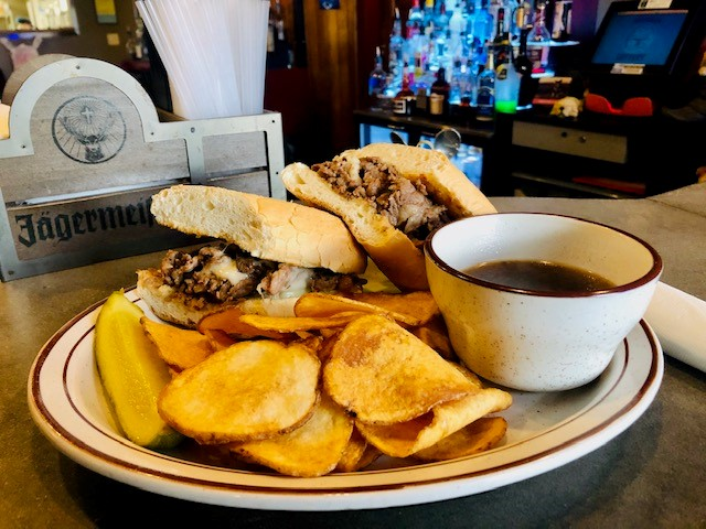 French Dip Sandwich: Sliced roast beef layered on a hoagie and topped with melted Swiss cheese. Served with hot au jus, chips and pickle spear