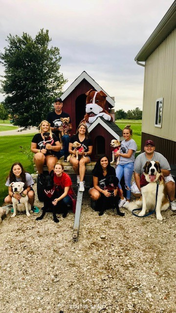 a group of people and dogs smiling at the camera
