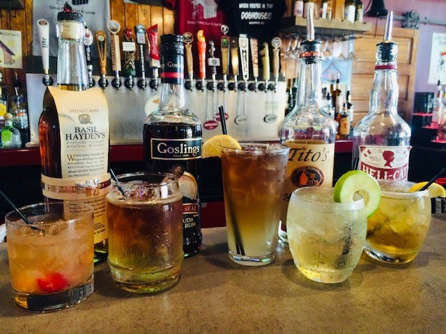 a variety of alcoholic drinks sitting on the bar