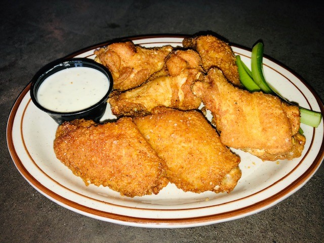 a plate of wings with ranch and celery on the side