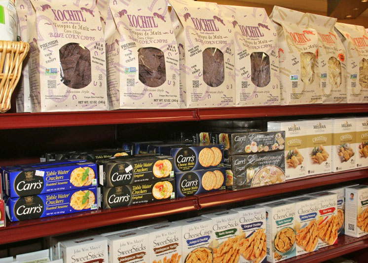 Shelves of products such as pasta, crackers, and cookies