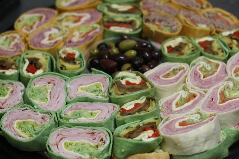 A tray filled with various pre-made sandwich wraps