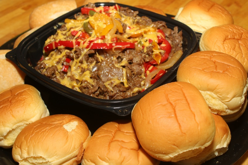 A philly cheesesteak platter for a catering event which consists of philly cheesesteak ingredients in the center of a tray surrounded by rolls
