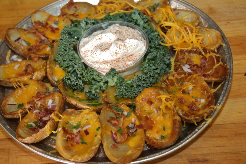 Loaded baked potatoes topped with cheddar cheese and bacon with sour cream in the middle of the platter