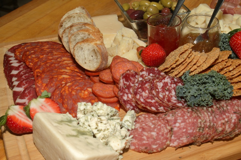 A charcutier board filled with crackers, salami, pastrami, pepperoni, various cheeses, fruit, bread, and jam