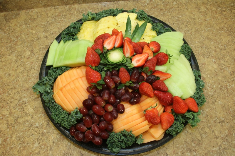A fruit platter with fruit such as pineapple, cantaloupe, strawberries, and grapes.