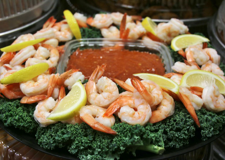 Shrimp surrounding a plastic container of cocktail sauce on a platter