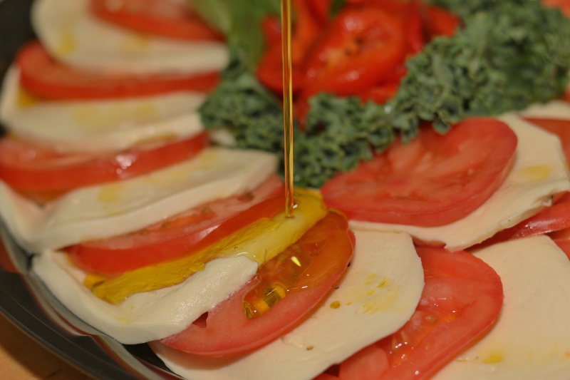 A mozzarella and tomato platter with olive oil dripping on top of it