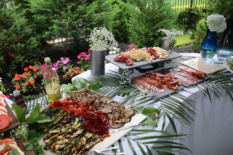 The buffet table at a catering event filled with trays of various dishes