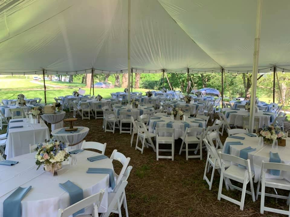 Many tables set with linen and chairs under a tent at a catering event