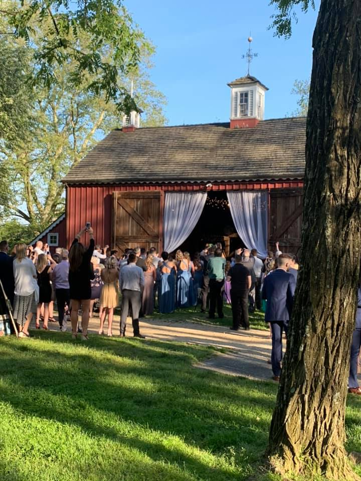 A catering event with guests walking into the barn
