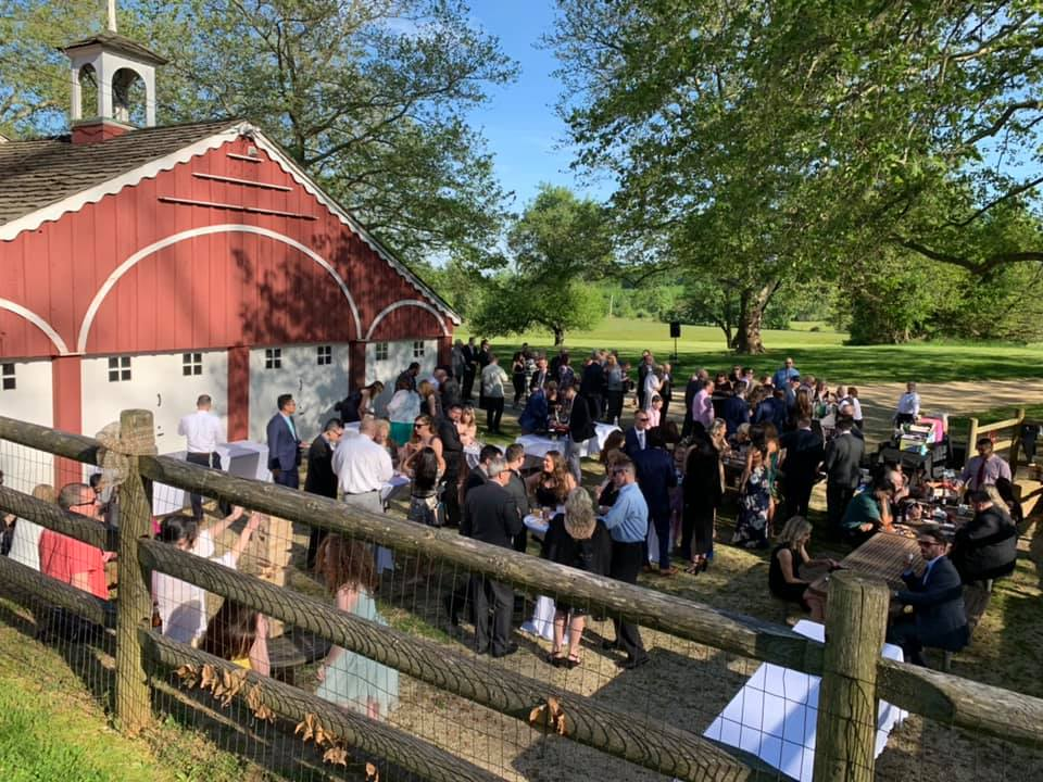 A catering event with guests dancing in front of the barn