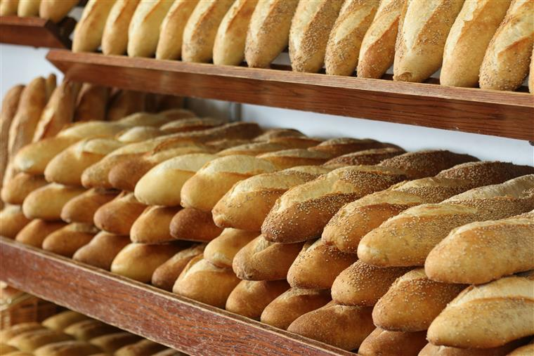 Italian bread piled on top of each other on wooden shelves