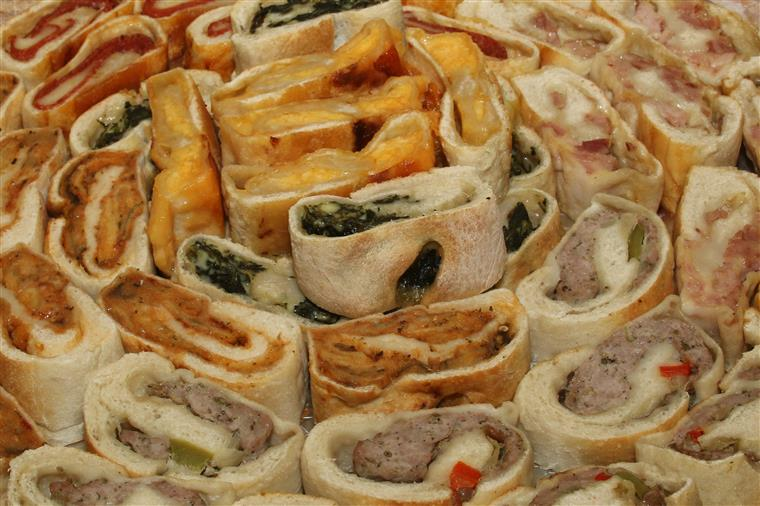 A tray full of stuffed bread. Half are stuffed with spinach and cheese, the other half is stuffed with roasted red peppers and mozzarella