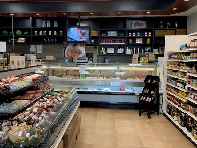 The front counter of Demarco's with many shelves filled with grocery items ad a display case filled with pre-made food