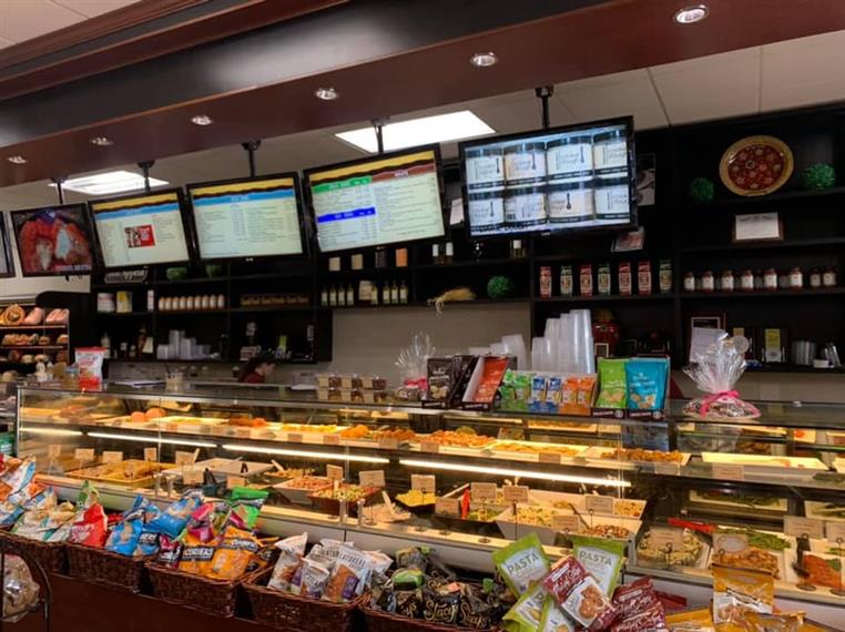 The front counter at DeMarco's with TV's above the Countertop and refrigerated shelves filled with to-go items