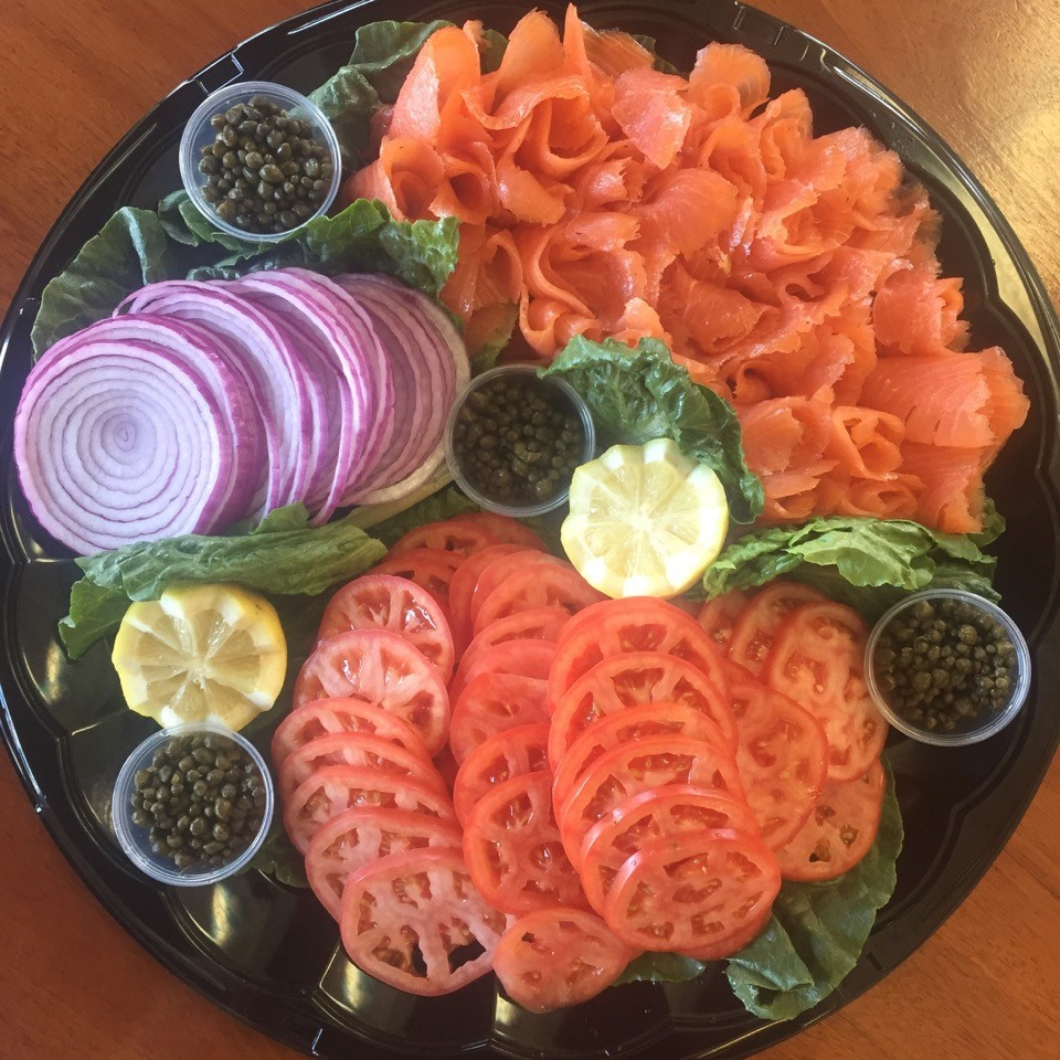 tray of sliced raw onion, sliced tomato, lox, lemon and capers